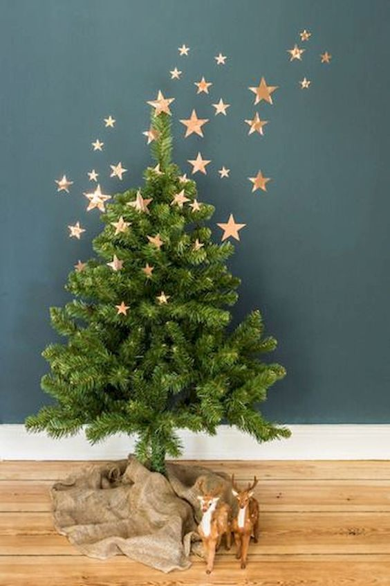 a small Christmas tree with burlap on the floor and copper foli stars as decor going up to the wall