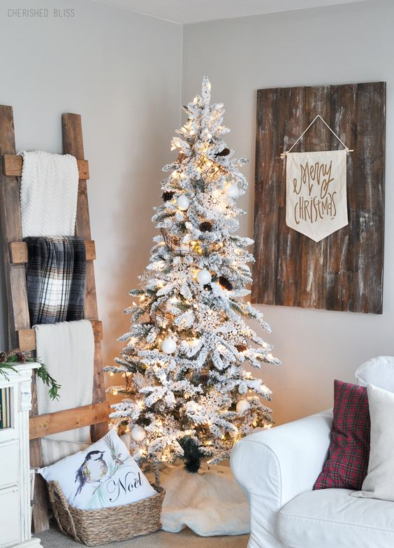 white ornaments, lights and pinecones make the flocked tree look very natural and will be ideal for Scandi interiors