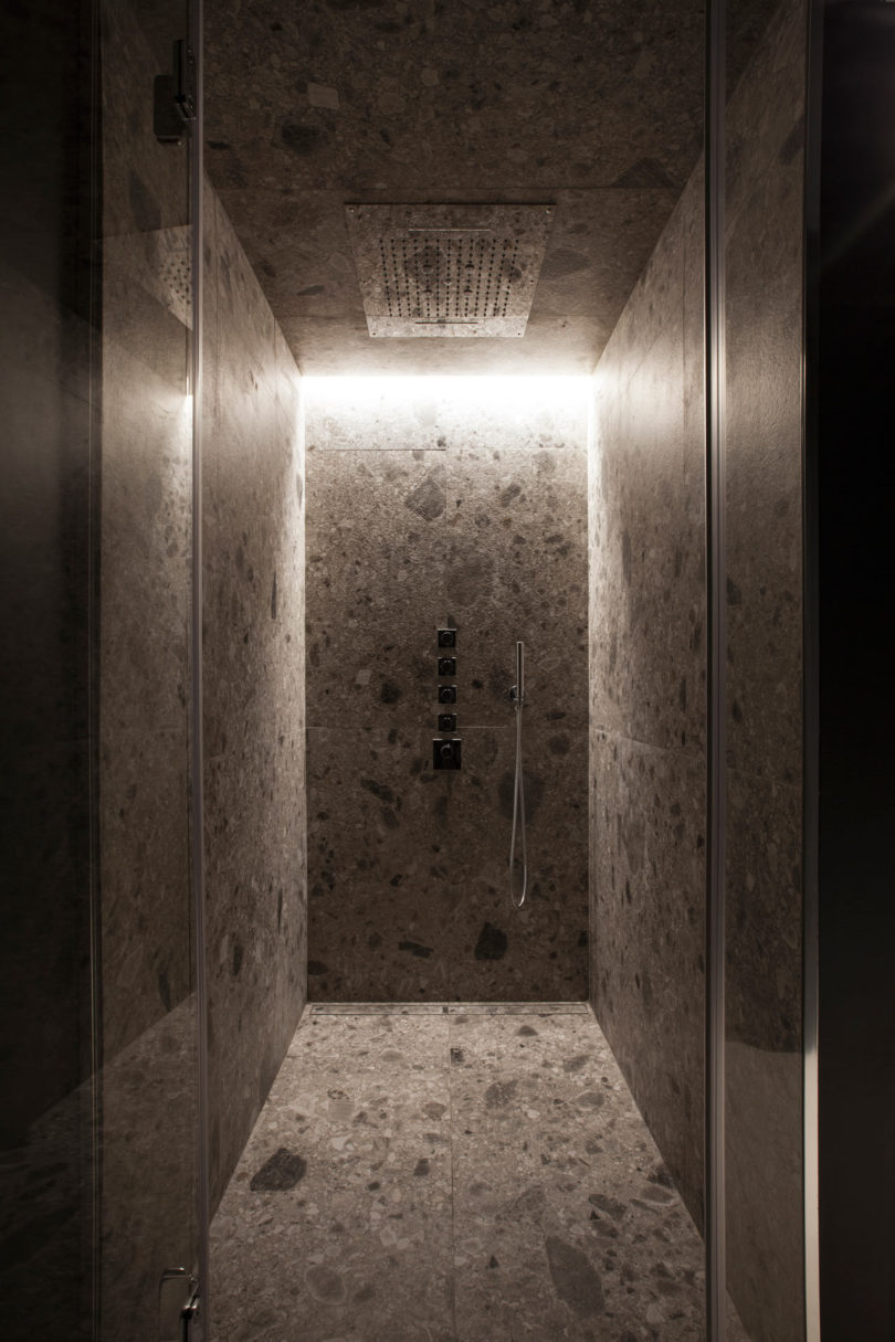 The second bathroom features a shower clad with stone