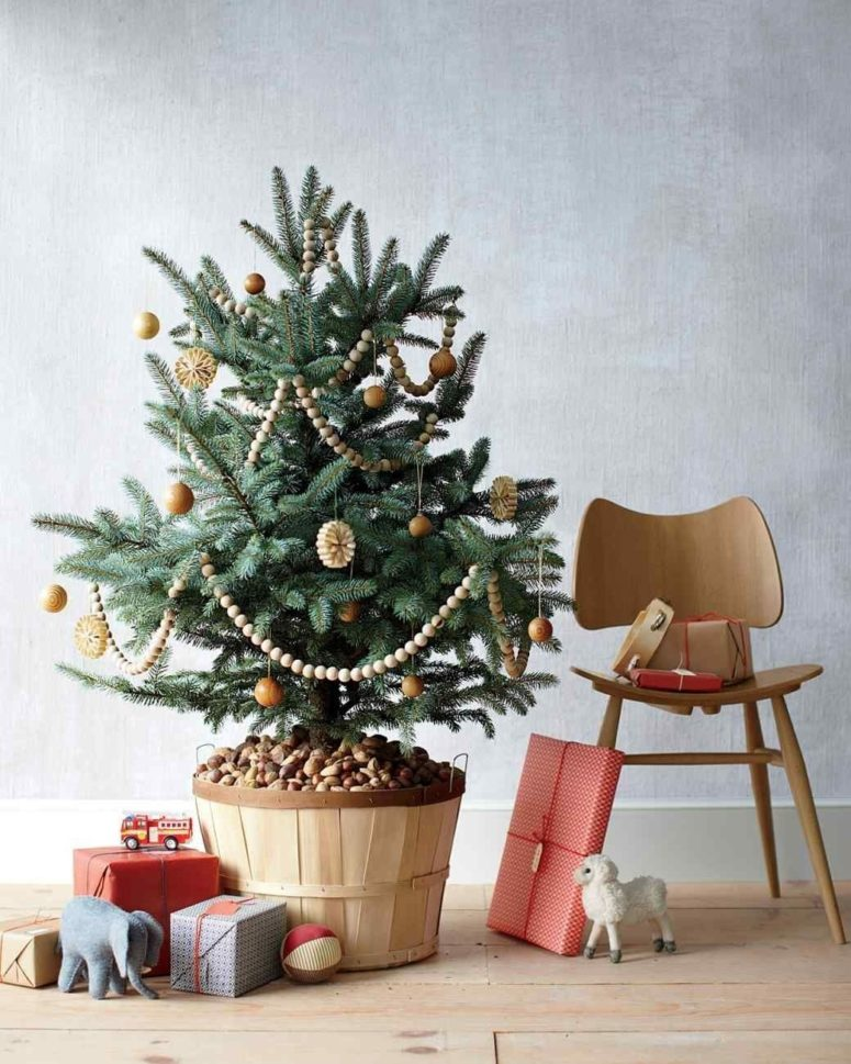 a Christmas tree decorated with wooden ornaments, bead garlands and paper ornaments in a wooden basket with pebbles