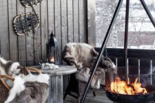 12 a cabin-style terrace with wicker chairs and a wooden table, faux fur and a large suspended fire bowl