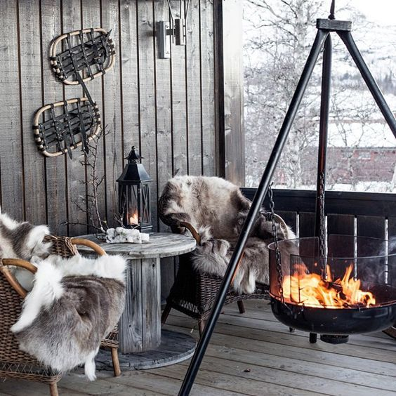 a cabin style terrace with wicker chairs and a wooden table, faux fur and a large suspended fire bowl