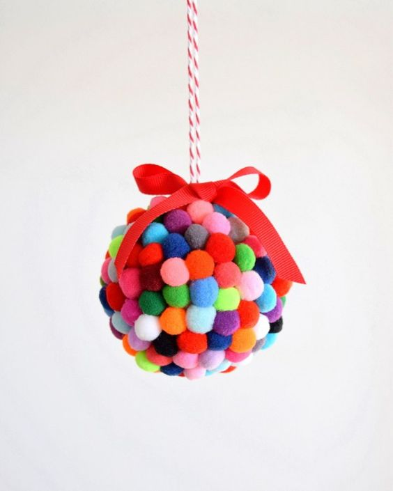 a colorful small pompom ornament with a bow on top is a fun idea to decorate your Christmas tree
