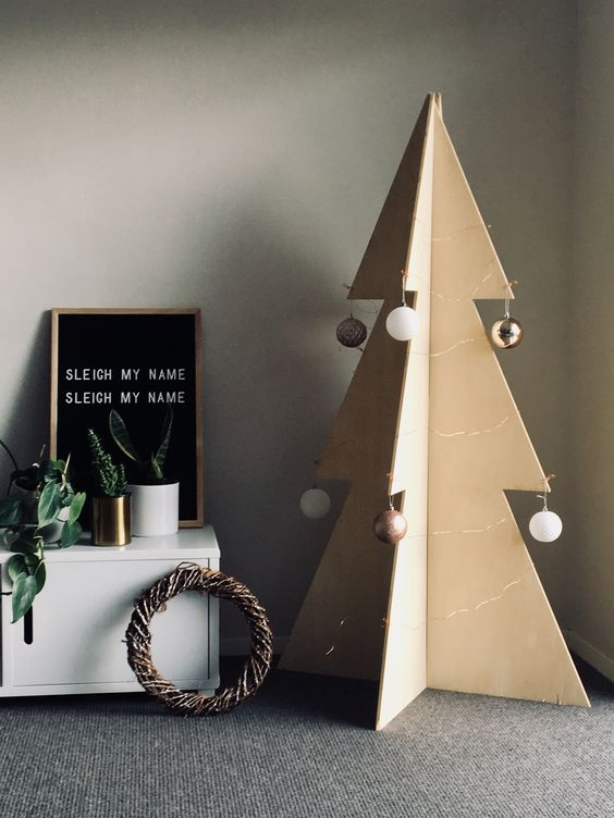 a large plywood Christmas tree decorated with several ball ornaments on each side for a minimalist look