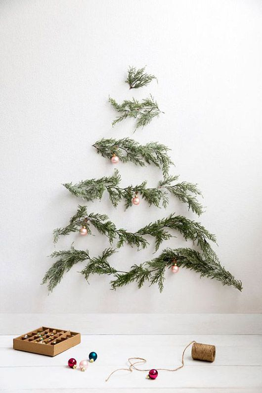 a minimalist wall-mounted Christmas tree of evergreens and little copper ornaments on them for an airy feel