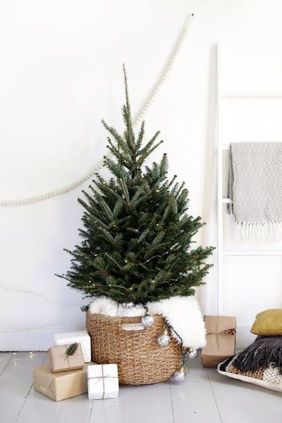a modern Nordic tree with LEDs in a basket base with faux fur and vintage lights hanging down