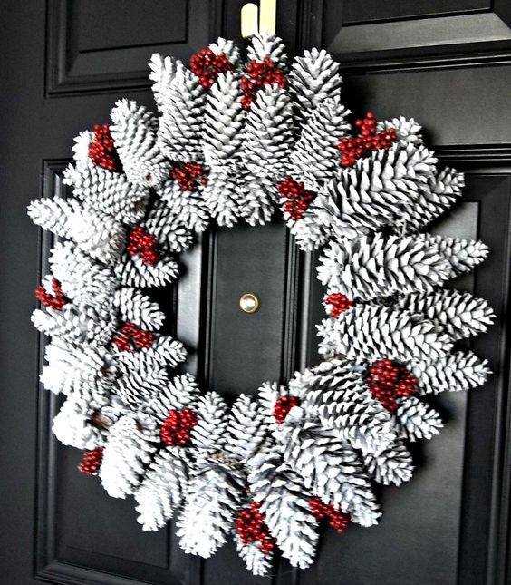 a snowy pinecone wreath with fake red berries is a bold idea for Christmas and it's very easy to make