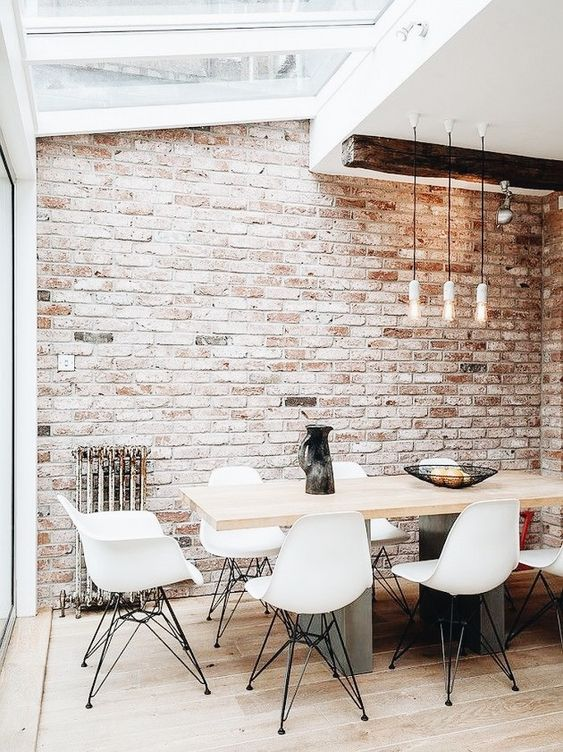 an all-neutral space spruced up with a single vintage brick wall  and a vintage metal stand