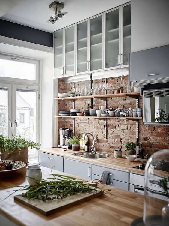 an exposed brick wall and wooden countertops for a modern rustic kitchen