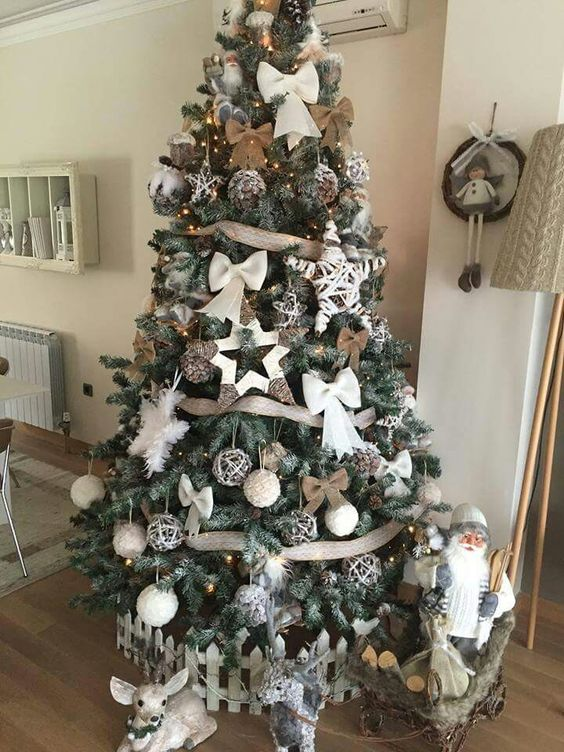 a beautiful rustic Christmas tree with burlap bows and ribbons, fluffy snowflakes, bows, vine ornaments and yarn balls