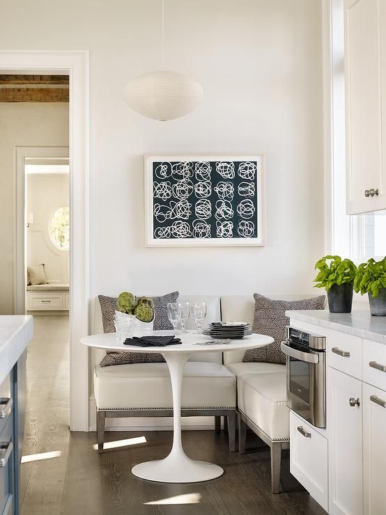 a cozy eat in kitchen nook with an L shaped bench and a round small table is what you need for breakfasts