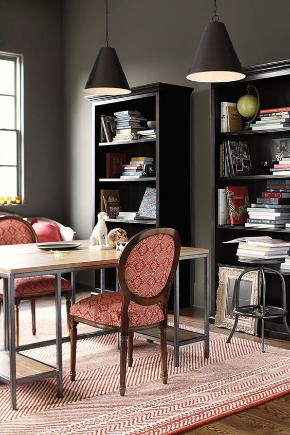 a dark and stark masculine space is balanced with red linens and red upholstery of the furniture