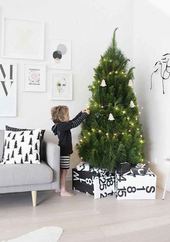 a modern Nordic tree with lights and white tree-shaped ornaments plus geometric ones