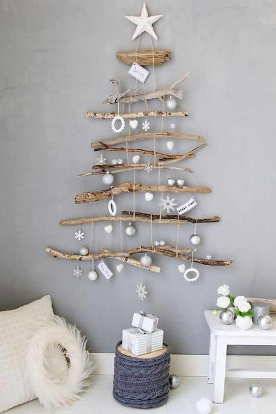 a natural wall-mounted Christmas tree of various branches and with white and silver ornaments hanging down