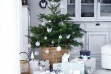 13 a small Christmas tree with lights and white ornaments plus a basket for a modern feel