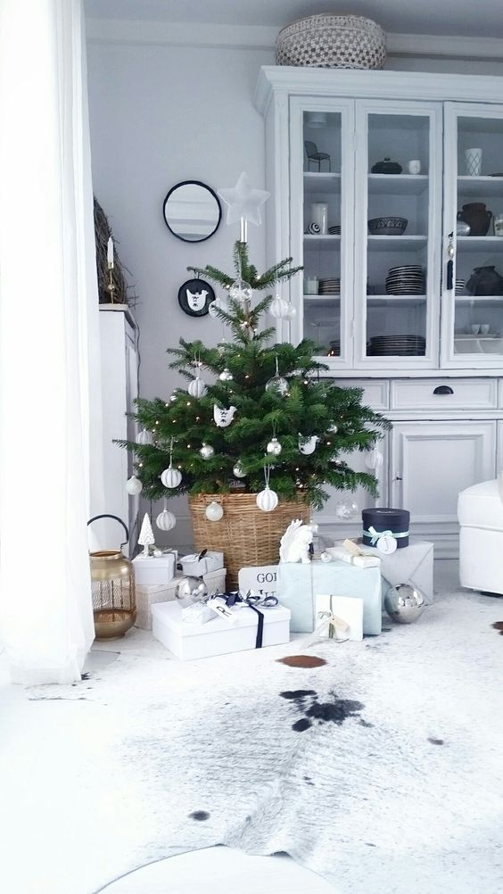 a small Christmas tree with lights and white ornaments plus a basket for a modern feel