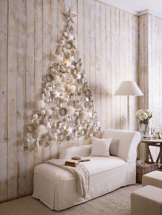 a subtle white Christmas tree of white ornaments and fluffs plus a star on top is realized right on the wall