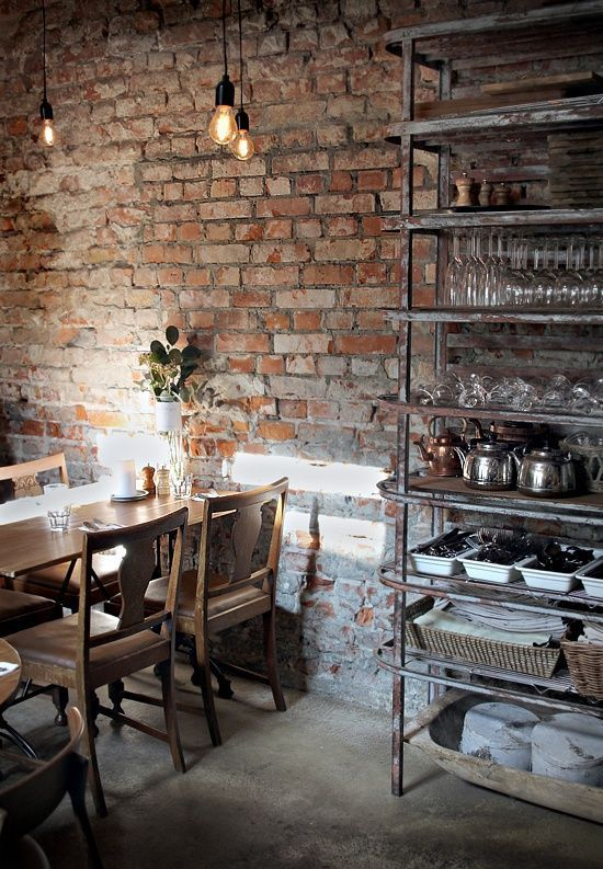 an exposed brick wall and vintage shabby metal furniture instantly make the dining room industrial