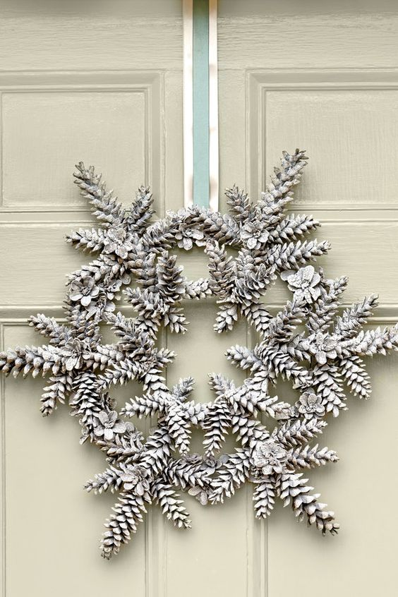 a Christmas wreath made of snowy pinecones and ribbon is a super creative and interesting idea