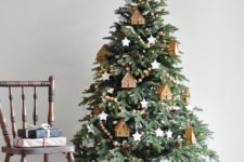 14 a cozy Christmas tree with wooden bead garlands, wooden tree ornaments and pinecones plus lights all over