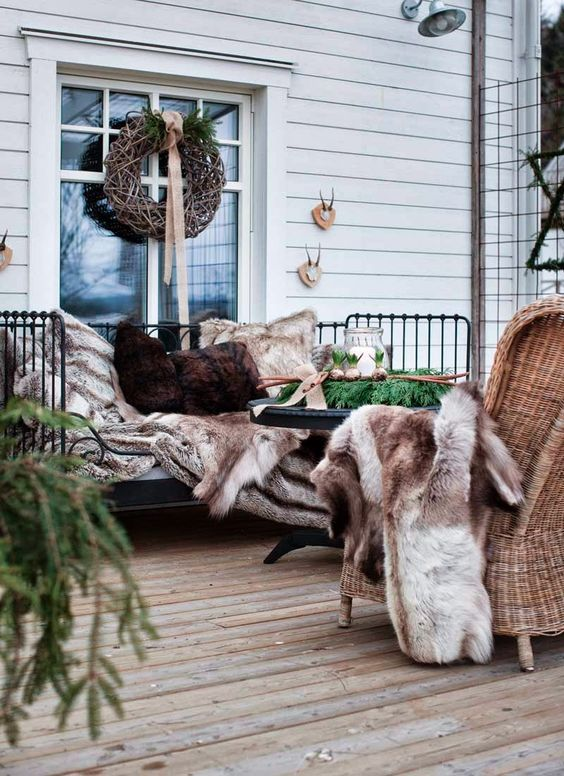 a cozy winter terrace with a metal bench, wicker chairs, faux fur throws and pillows, evergreens and candle lanterns
