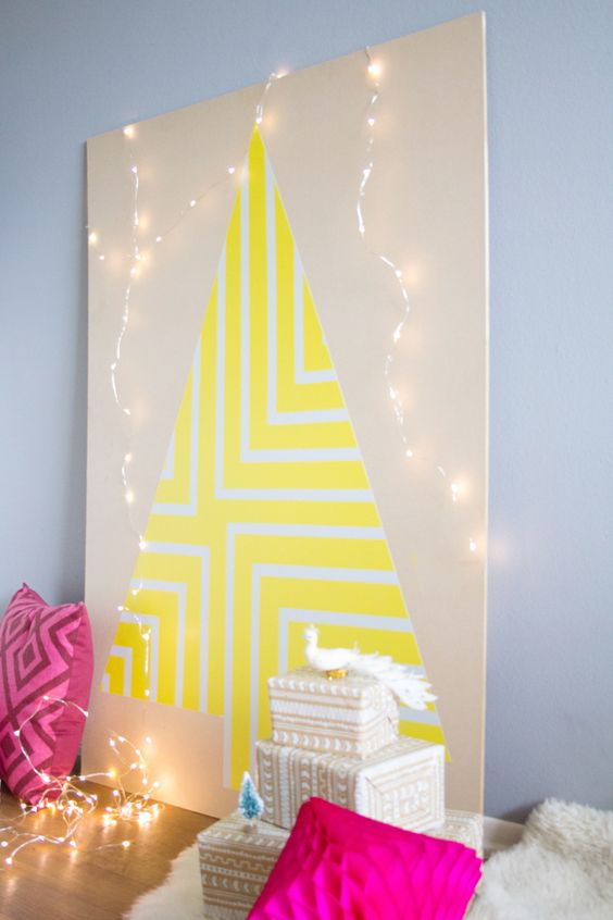 a neon yellow geometric Christmas tree on a plywood sheet with lights around for a colorful space