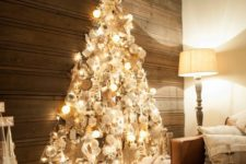 14 a shiny wall-mounted Christmas tree made with lights on the contour and with lots of silver, pearly and white ornaments inside