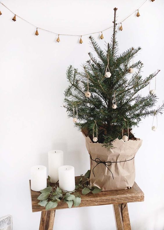 a small Christmas tree with wooden ornaments wrapped into kraft paper for a super natural feel