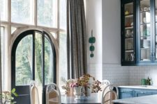 14 an elegant kitchen eat-in space right in the center, with a vintage dark wood table and airy rattan chairs