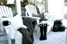 15 a duo of wooden chairs with pillows, blankets and faux fur, potted plants and a whitewashed deck for a Nordic touch
