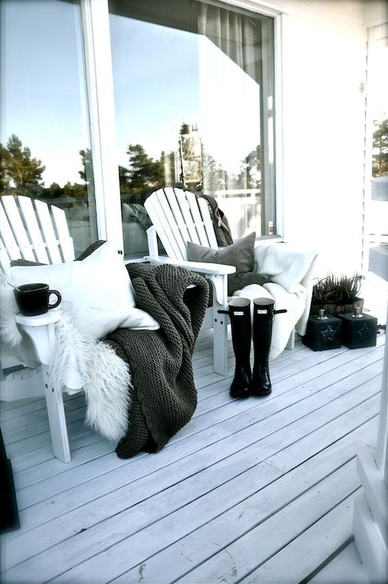 a duo of wooden chairs with pillows, blankets and faux fur, potted plants and a whitewashed deck for a Nordic touch