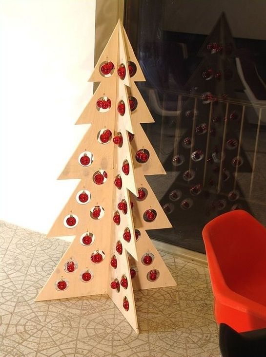 a plywood Christmas tree with holes and little red ornaments hanging in them for a minimalist or Scandinavian space