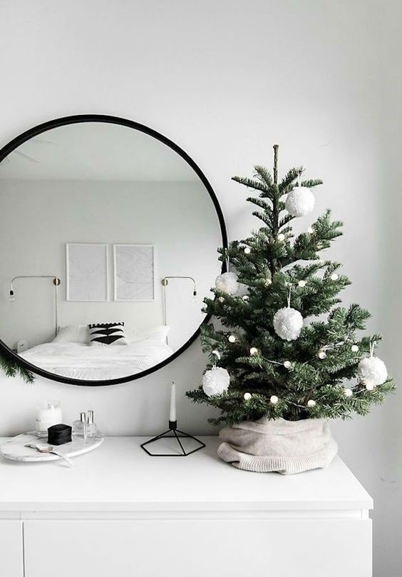 a small tree covered with neutral knit, small and largre pompoms in white for laconic modern decor