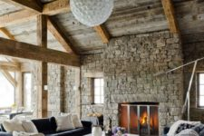 15 much stone, wooden beams and comfortable modenr furniture upholstered with velvet and a cowhide rug