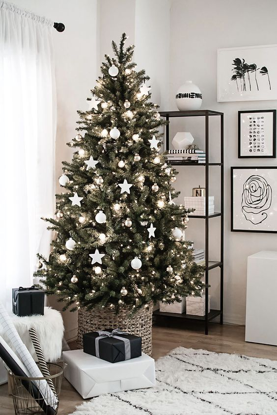 a Scandinavian Christmas tree decorated with white ball and star ornaments, metallic ornaments plus lights in a basket