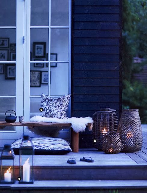 a Scandinavian space with lots of candle lanterns, pillows and faux fur for a real hygge feeling