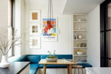 16 a colorful eat-in kitchen nook with an L-shaped teal bench and a wooden table doesn't take much space