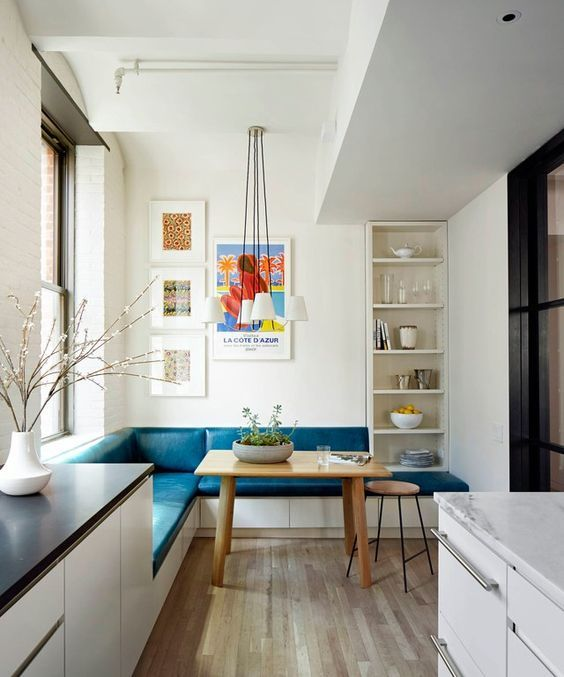 a colorful eat in kitchen nook with an L shaped teal bench and a wooden table doesn't take much space