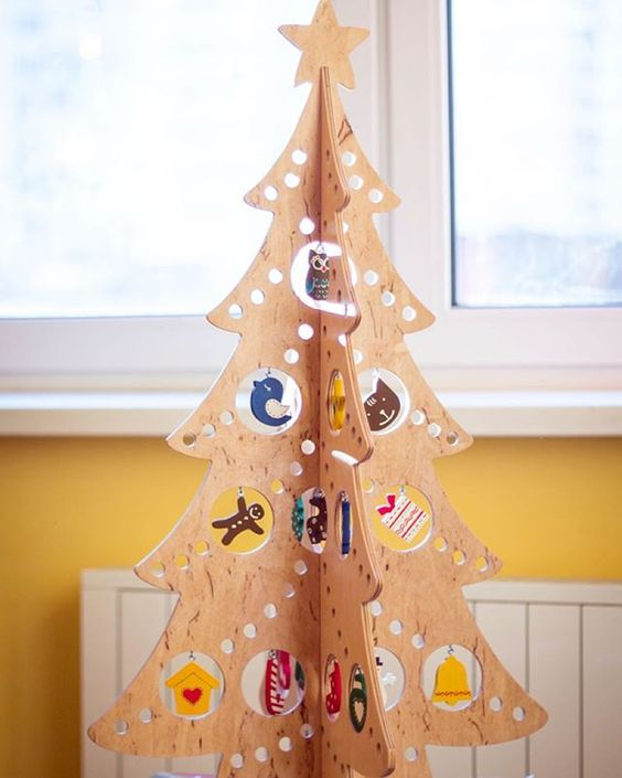 a plywood Christmas tree with holes of various sizes and ornaments hanging in them for a fun and creative look