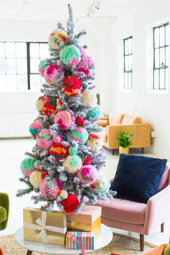 a silver Christmas tree decorated with colorful oversized pompoms for a bold statement
