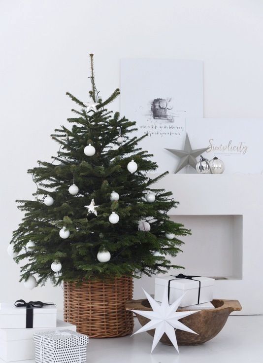 a small tree in a basket styled with white ornaments screams Scandinavian or minimalist
