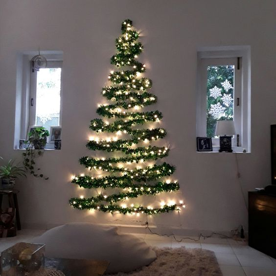 a wall-mounted Christmas tree silhouette done with an evergreen garland and lights for a modern space