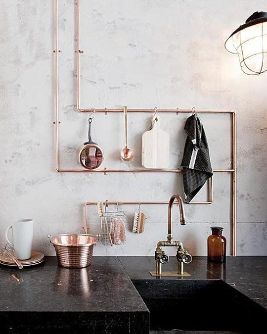 exposed copper piping doubles as utensil storage in this industrial kitchen