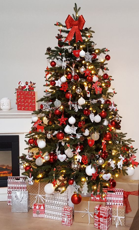a bold traditional Christmas tree with red and white ornaments of various shapes, lights and with a red bow on top