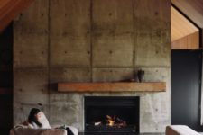 17 a concrete fireplace wall, a metal mantel and a gable roof clad with wood