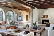 17 a modern rustic living room decorated with a variety of materials, wood, stone, faux fur, sisal and jute