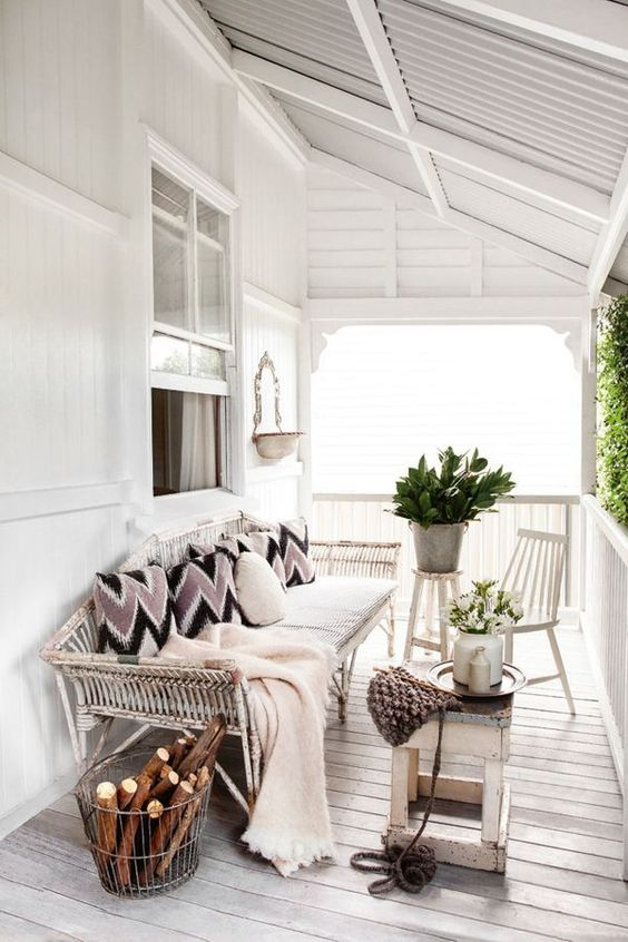 a shabby chic bench, chairs and stools, a metal wire basket with firewood, potted greenery and blooms