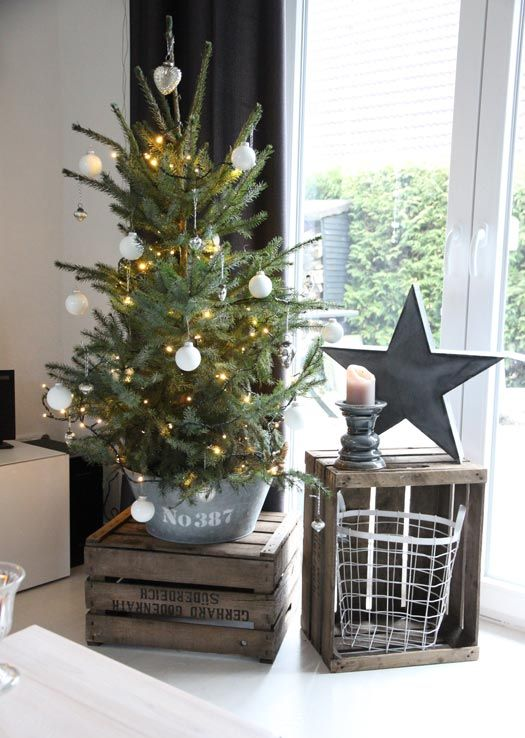 a small tree in a galvanized bucket used as a tree base with lights and white ornaments is a great rustic idea for Christmas