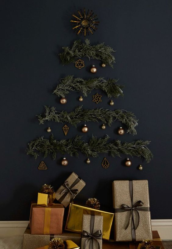 a stylish wall-mounted Christmas tree on a black wall of evergreens, lights and brass ornaments