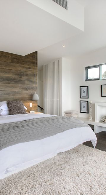 a wood wall and a fluffy rug add interest to the space and make it catchier and brighter